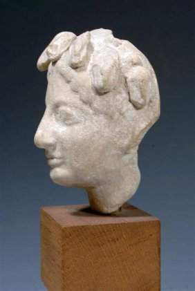 A Greek Terracotta Head Of A Youth, Archaic Style