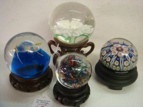 Four Paperweights With Wooden Stands: