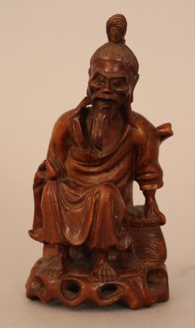 Asian Wooden Sculpture Of A Man Sitting On A Wooden