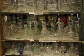 Shelf Of Clear Glass And Crystal Decanters Etc