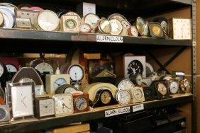 Two Shelves Of Alarm Clocks.