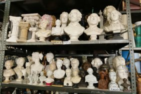 Two Shelves Of Plaster And Metal Busts In