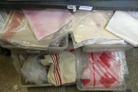 Two Shelves Of White And Red Hand Towels.