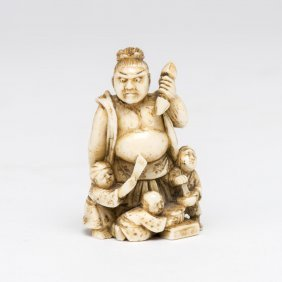 An Ivory Netsuke Of A Temple Guardian Holding