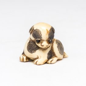 An Ivory Netsuke Of A Seated Puppy With Onyx Eyes,