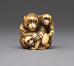 An Ivory Netsuke Of A Seated Monkey And Two Young With