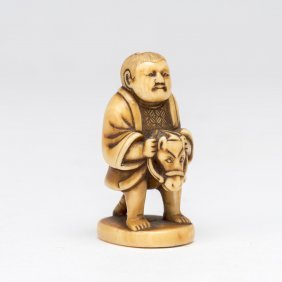 An Ivory Netsuke Of A Boy Riding A Toy Horse