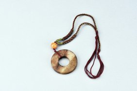 An Archaic Jade Disc With Amber Bead
