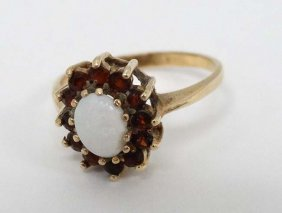 A 9ct Gold Ring Set With Central Opal Bordered By 12