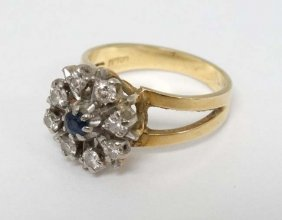 An 18ct Gold Ring With Central Sapphire Bordered By 8