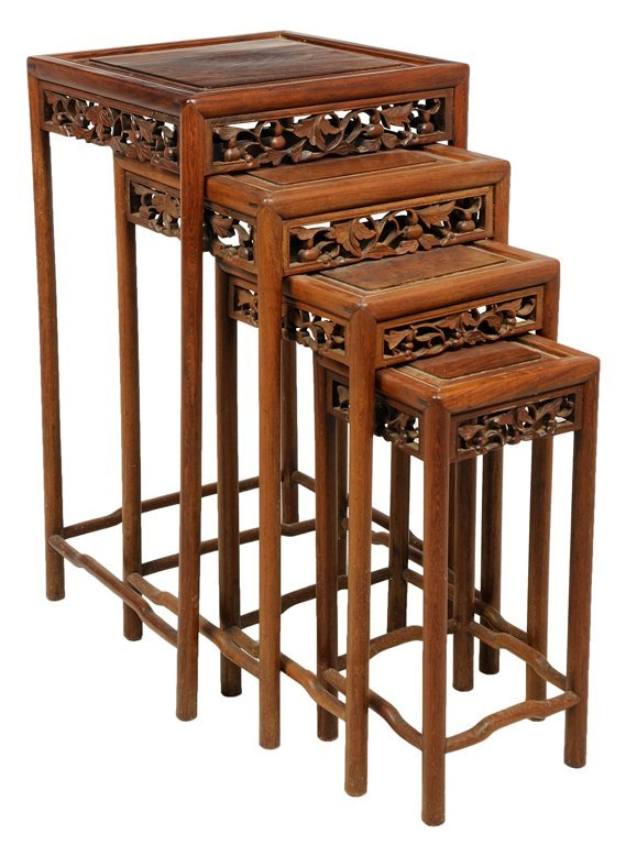 A set of four chinese carved wood nesting tables lot