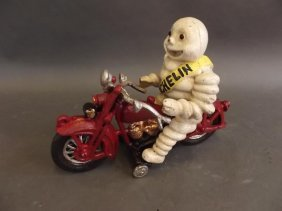A Cast Iron Figure Of The Michelin Man Riding A