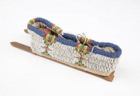 A Miniature Beaded Cradle Board With Skookum Doll