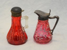 (2) Cranberry glass syrup pitchers with silver plated