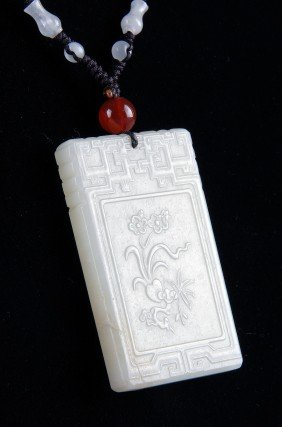 A CHINESE CARVED PALE CELADON JADE PENDANT, Of Rec