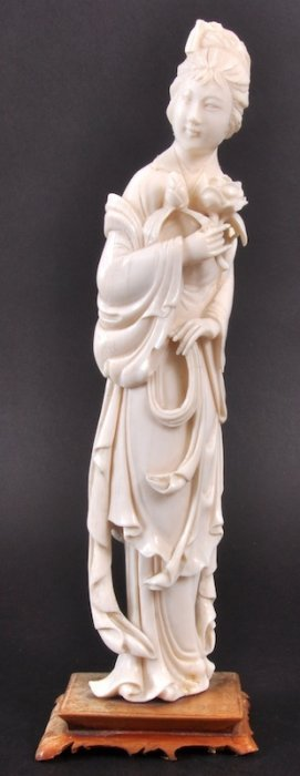 A CHINESE CARVED IVORY FIGURE OF A YOUNG GIRL Holdi