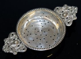 A Silver Two Handled Tea Strainer.
