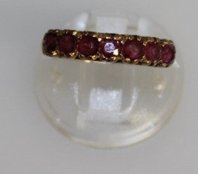A Gold Ring Set With Seven Pink Stones.