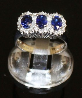 A Three Stone Sapphire And Diamond Cluster Ring Set In