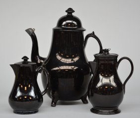 A Coffee Pot And Two Cream Jugs In Black Glazed