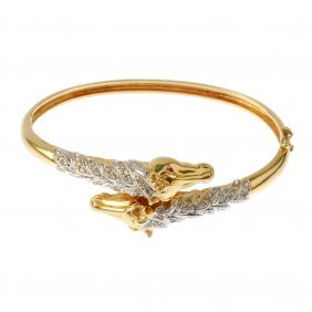 An 18ct Gold Diamond And Ruby Horse Hinged Bangle.